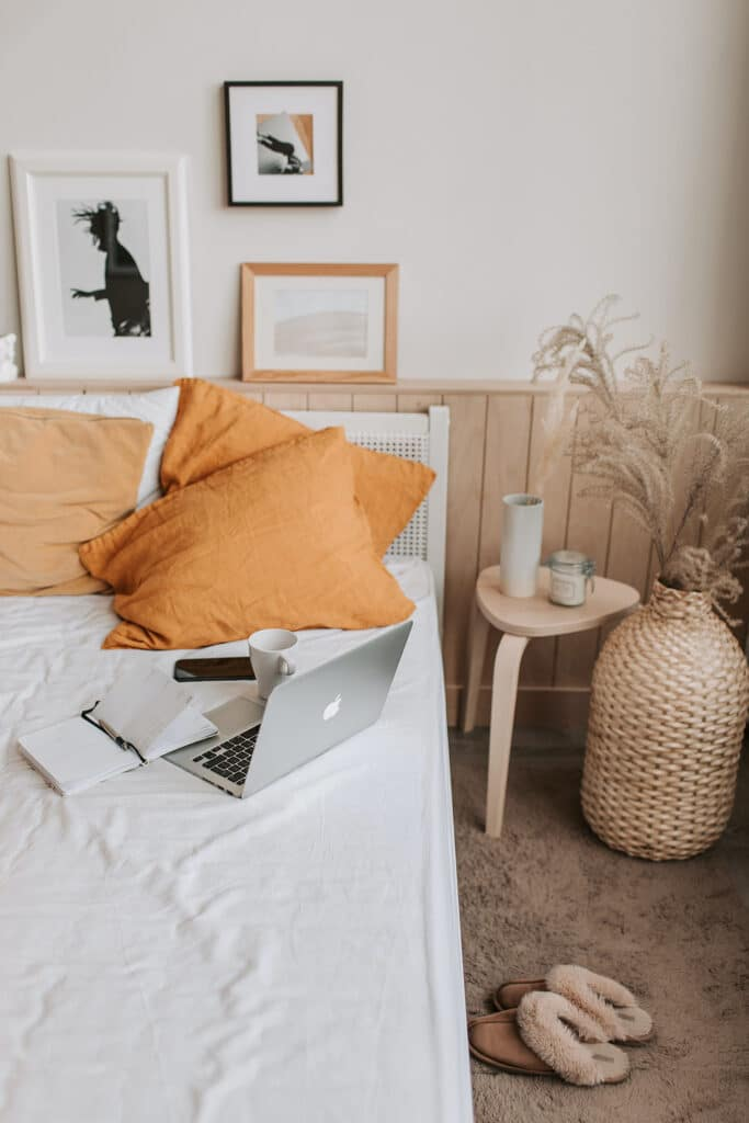 A beautiful modern bedroom showing paintings on the walls, a soft brown carpet and a pair of fluffy slippers by the bed, while a laptop, journal, and coffee cup sit on the edge of the bed by orange linen cushions, showing the comfort and joy of self-care journaling