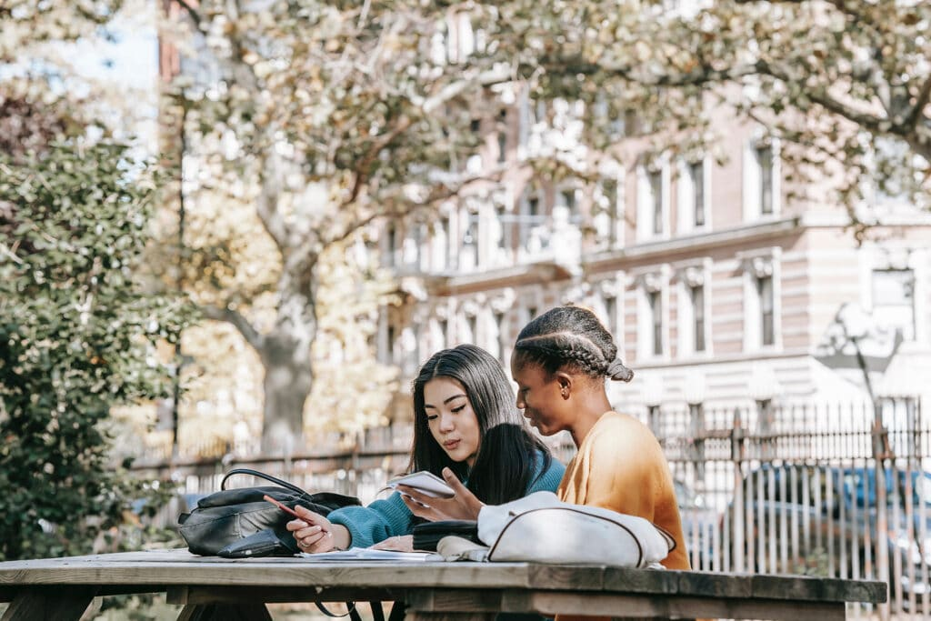 Two women of color are studying together on a wooden picnic table in a courtyard, their backpacks are on the table beside them, and they're sharing notes as they learn about restorative justice in the classroom together