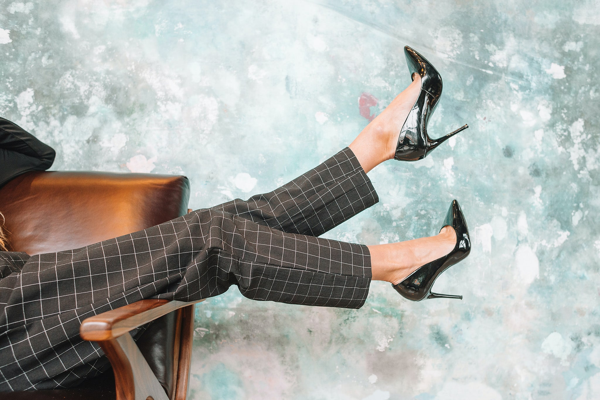 A woman is sitting in a brown leather chair out of frame while her legs extend into frame showing brown checkered pants and shiny black patent lather high heels, illustrating the gender norms persistent in posteminist narratives about female leaders