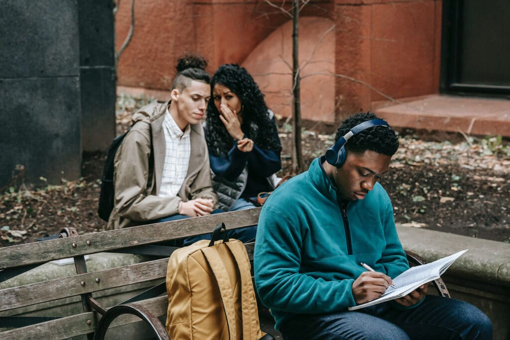 A Black man sits in a teal sweatshirt listening to music on headphones and studying in a book on his lap while two classmates are sitting behind him and whispering to one another, representing the importance of addressing harms in the classroom through restorative justice