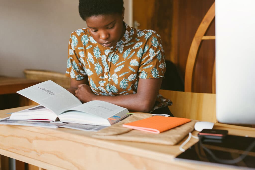 A Black woman in a patterned shirt is studying in a contemporary library with her textbooks in front of her, studying restorative justice in the classroom to address harms