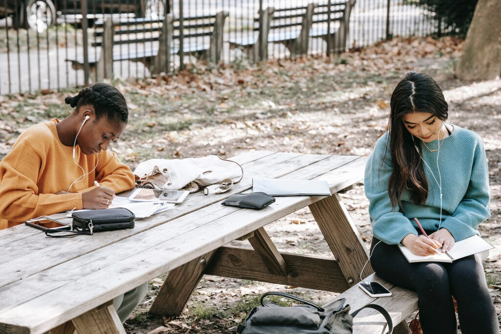 Two women of color who are friends are journaling together in a wooden picnic table in a park, showing how the self-care writing prompts can be shared with friends on a collective self-care day