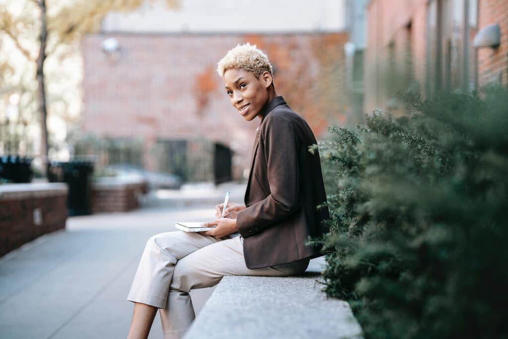 A Black woman with short blonde hair in a brown and beige suit is sitting outside in an urban garden courtyard, journaling in her lap and smiling in a moment of peaceful reflection and self-care