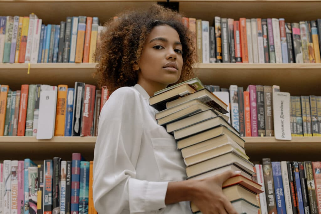 A Black woman is in a library in front of a big bookshelf, carrying a big pile of books in her hands, representing the endless reading and research required when doing a PhD
