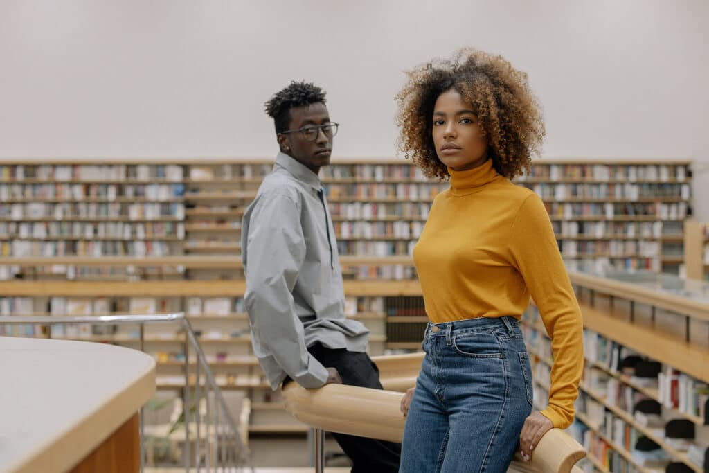 A young Black woman stands in the foreground of a modern library and a young Black man stands behind her, both looking intensely and thoughtfully at the audience, representing the vital friendships and connections we need to forge as people of color doing their PhDs