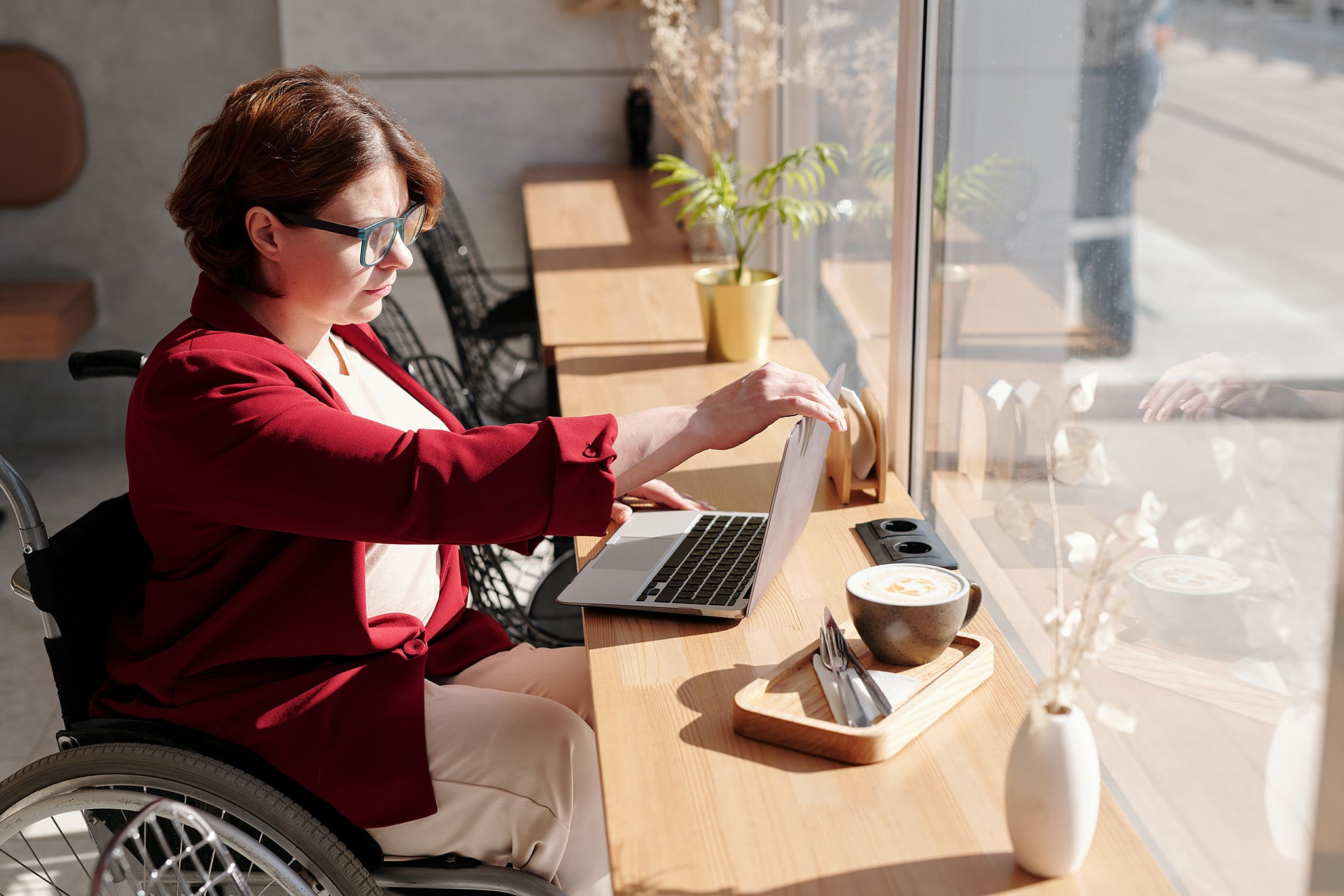 A woman in a maroon blazer in a wheelchair sits at a sunny window of a café, opening up her laptop by her coffee