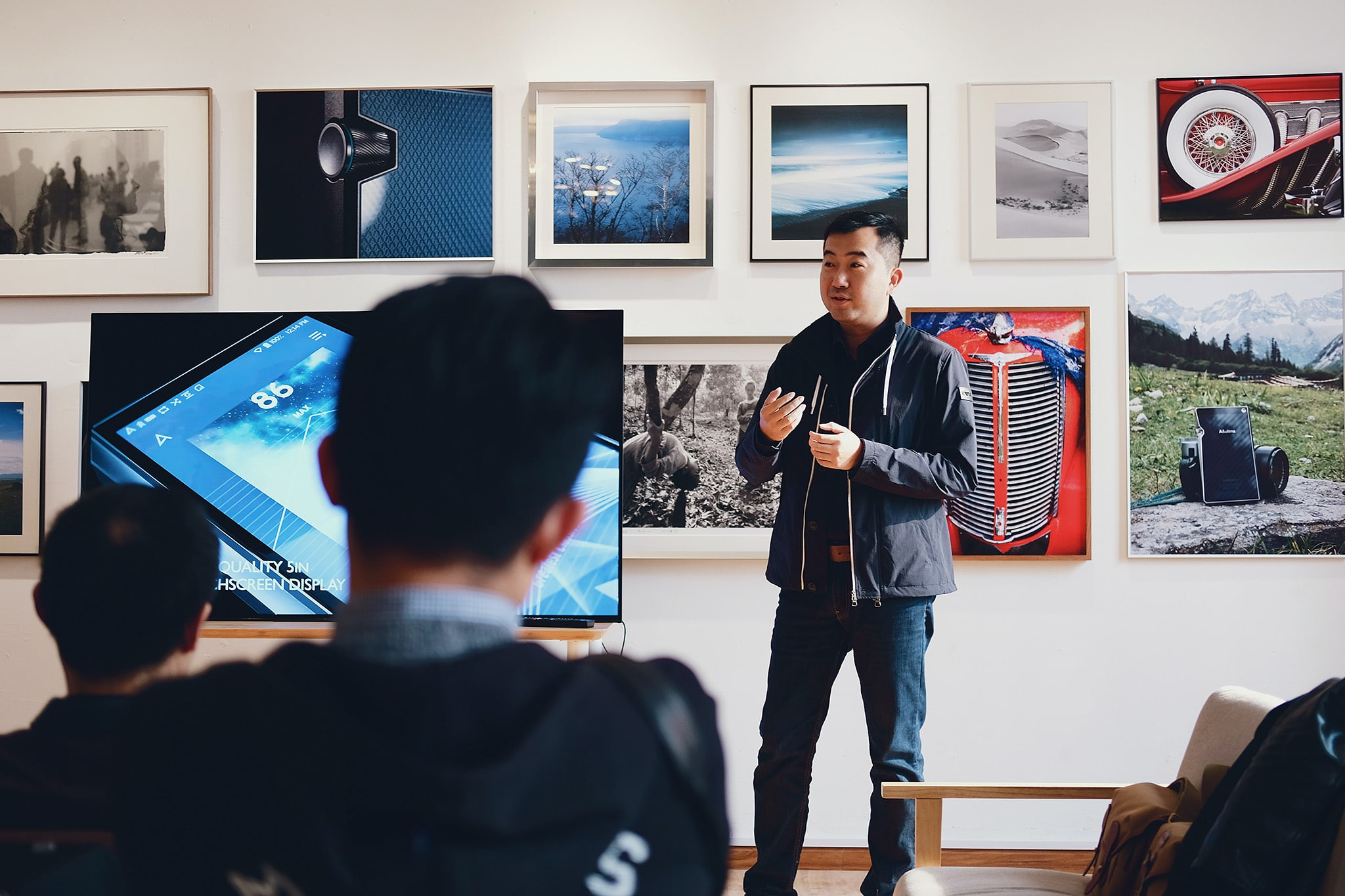 A seminar of students in a photography class with blurred backs of students in the foreground and an Asian lecturer at the front of the room standing in front of framed photographs, establishing restorative justice principles in his class