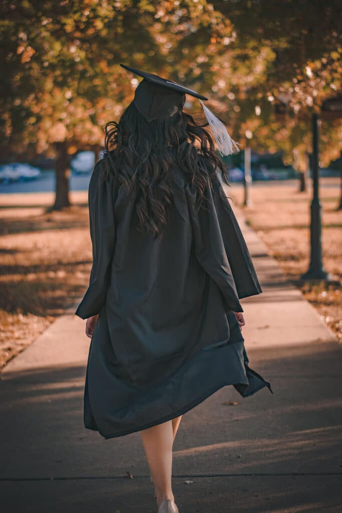 A woman of color is walking away from the camera wearing her black cape and gown at her PhD graduation